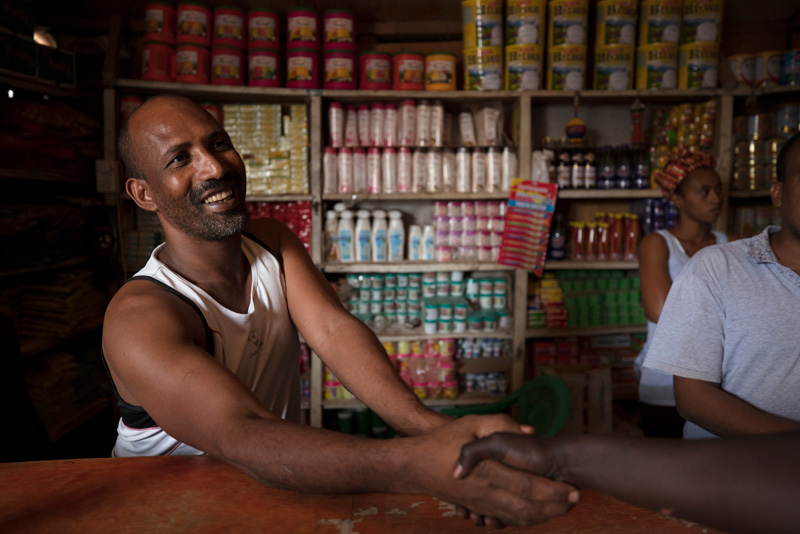 Mesfin Gitahon, refugee and owner of a food shop, greets and talks to customers in Kakuma.