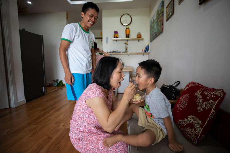 Thoa Ngo feeds her five-year-old son, Quan Le, while her husband Quang Le looks on. The three of them recently moved into the EcoHome Phuc Loi apartment building.