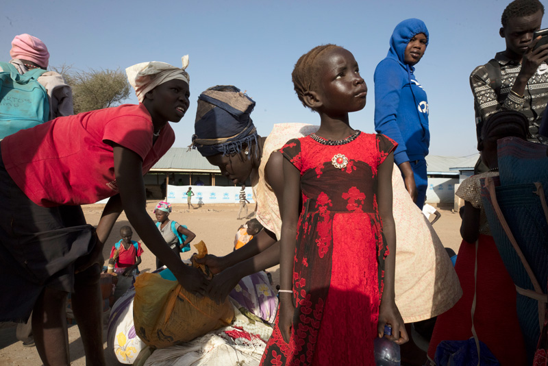 UNHCR helps hundreds of refugees cross the border near Nadapal, Kenya, as they flee South Sudan. Here, refugees wait at the reception center in Kakuma.