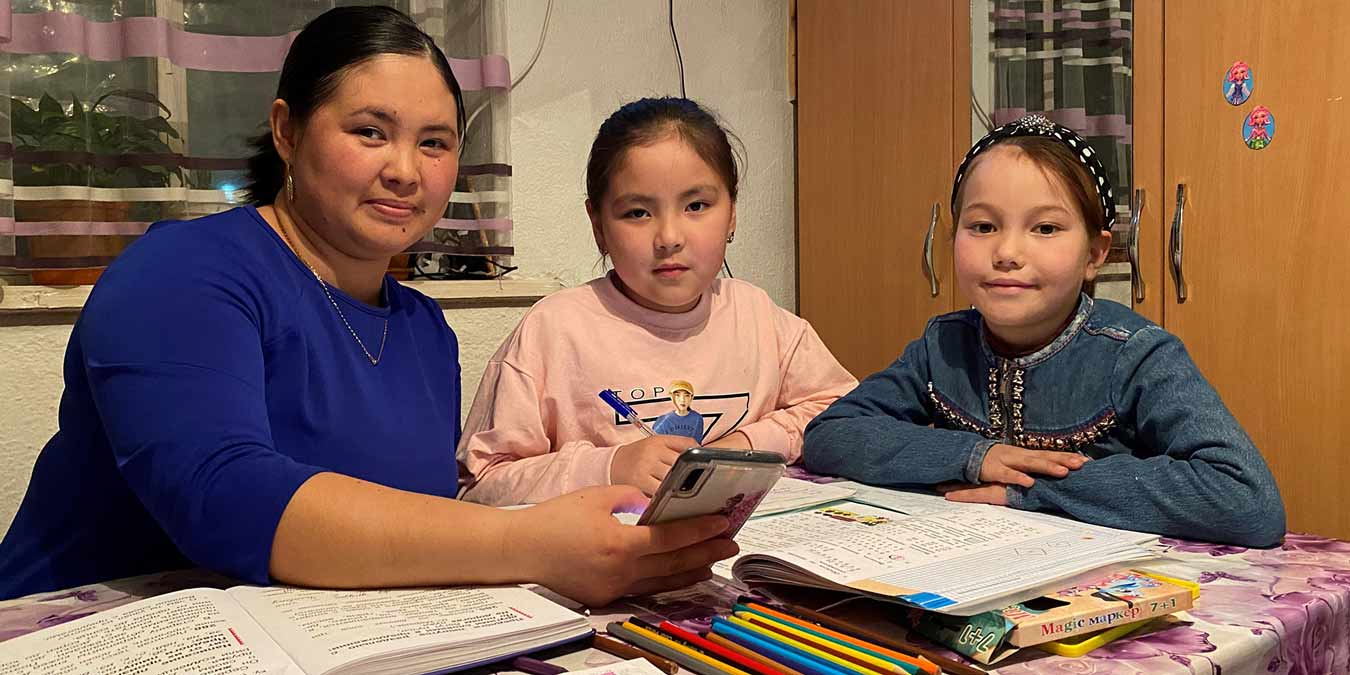 With no high speed internet connection, Meerim Arunova and her daughters work on remote lessons using only a mobile phone.