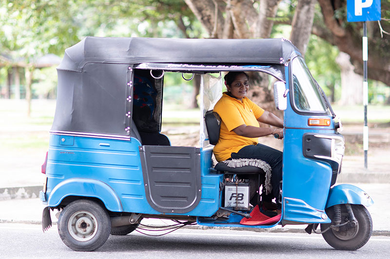 Lasanda Deepthi behind the wheel of her tuk tuk (three-wheeled auto rickshaw) in Colombo, Sri Lanka. Photo: Nadun Baduge