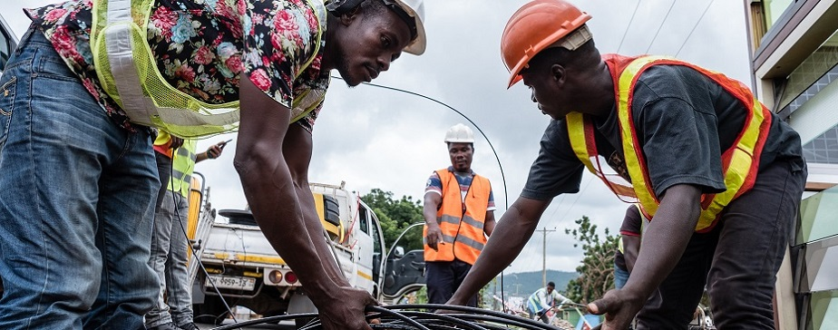 Workers laying fiber-optic cable in Ghana