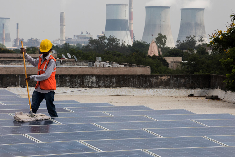 Solar panels installed on the rooftop of a government building in Gandhinagar contrast with a neighboring coal-fired power plant.
