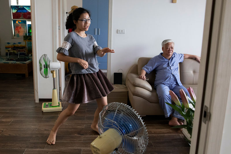 Twelve-year-old Giang Pham sings along with television videos in the family's new apartment.