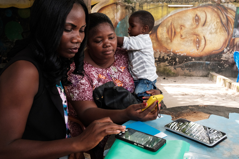 A MoMo Tap activator teaches Eugenie Brou Kouadio (right) how to use her device in Abidjan.