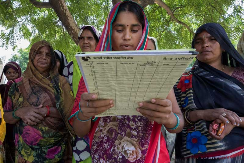 Malti Devi, an Utkarsh client, speaks to neighbors and members of her lending group in the village of Belwa.