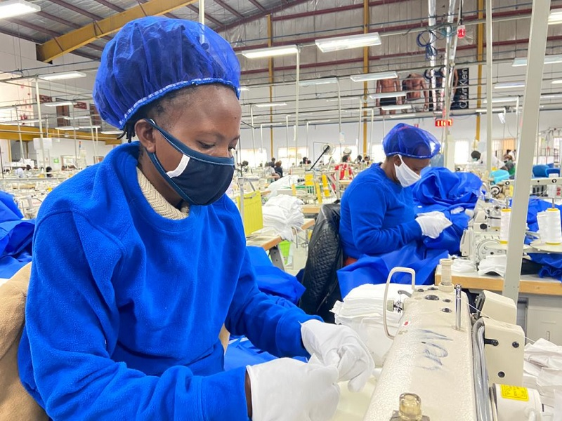 Workers at Hela Clothing in Kenya stitch PPE.