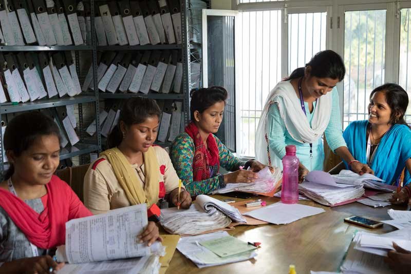 Employees of an all-women's micro-banking branch of Utkarsh work side-by-side at their office in the village of Harhua.