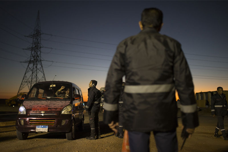 Private security guards inspect cars, trucks, and buses loaded with workers entering the Benban Solar Park.